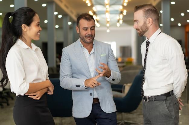 Drie positieve bedrijfsmensen die in bureauhal spreken