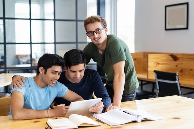 Drie positieve studenten die op tabletcomputer samen doorbladeren