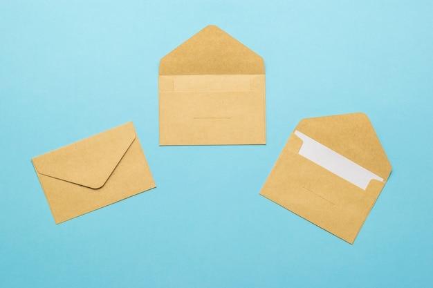 Drie postenveloppen op een lichtblauwe achtergrond. plat leggen.