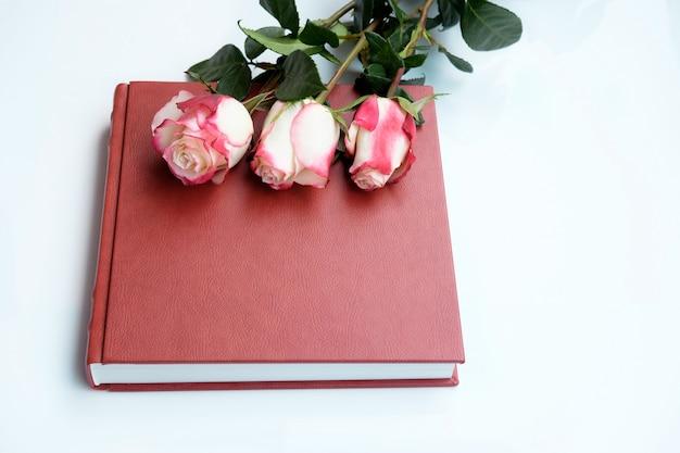 Drie prachtige rozen ligt op rood leer bedekt trouwalbum of trouwboek.