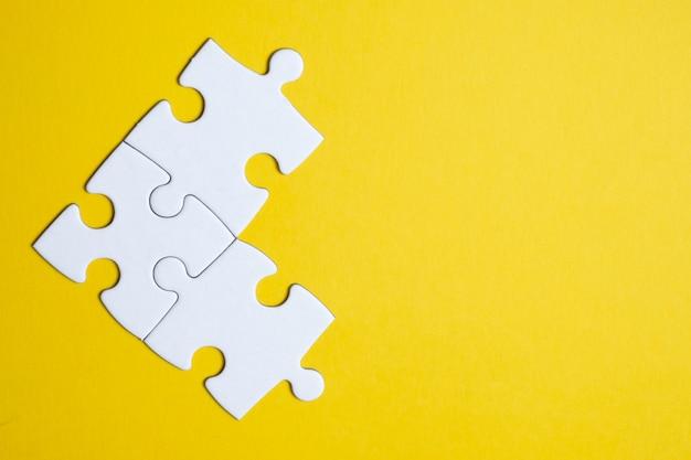 Drie puzzelstukjes verenigd op een geel. teamwerk.