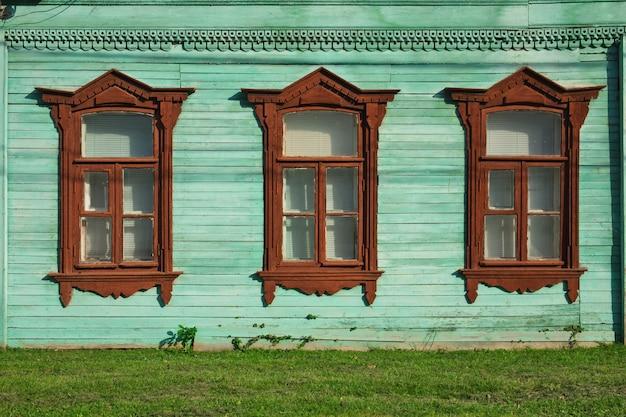 Drie ramen in rij van oud russisch huis versierd met houtsnijwerk traditionele architectuur