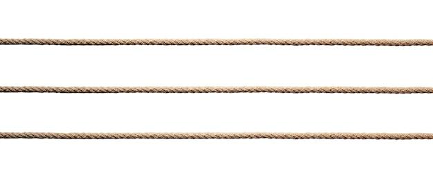 Drie rechte lijnen van gedraaide manilla touw geïsoleerd op een witte muur.