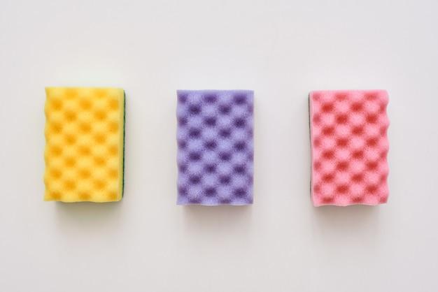 Drie reinigingssponzen geïsoleerde geelroze en paarse reinigingssponzen