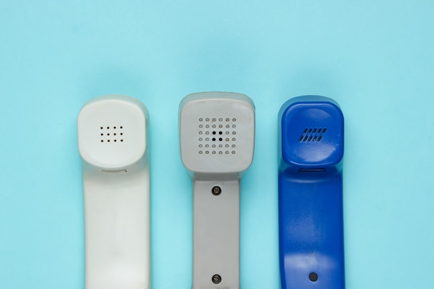 Drie retro telefoontoestellen op blauw