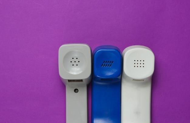 Drie retro telefoontoestellen op paars