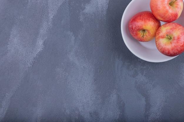 Drie rijpe appels op witte plaat op dark.