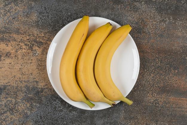 Drie rijpe bananen op witte plaat