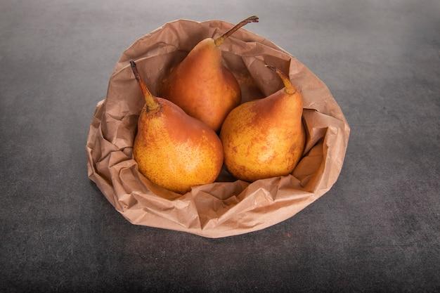 Drie rijpe gele peren in een ambachtelijke papieren zak op een tafel