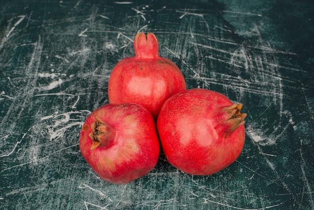Drie rijpe granaatappels op marmeren tafel.
