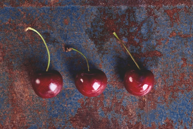 Drie rijpe kersen op de oude tafel