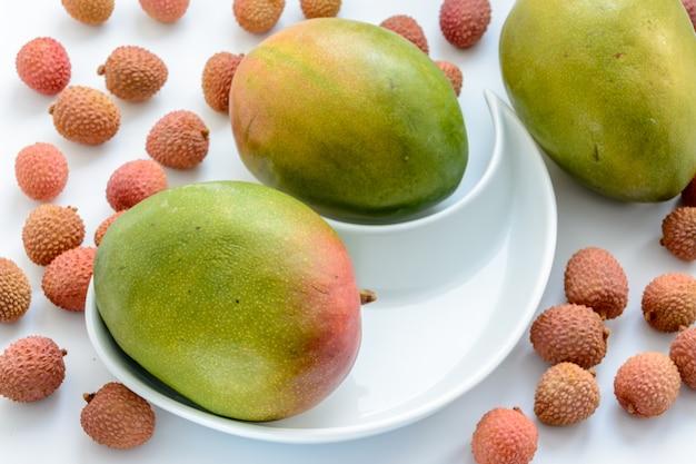 Drie rijpe mango's omgeven door rijpe lycheevruchten op een bord op een witte achtergrond.