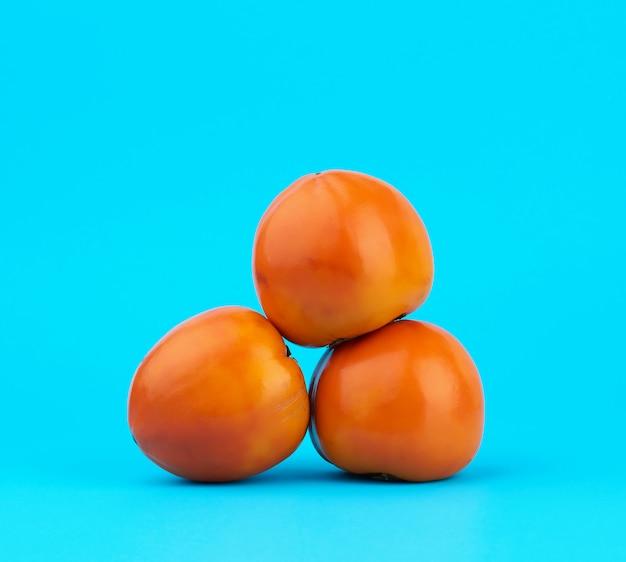 Drie rijpe oranje kaki