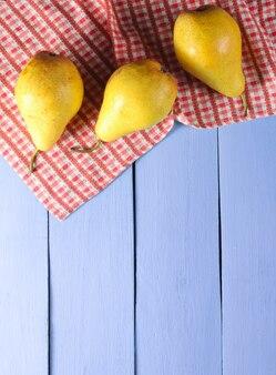 Drie rijpe peren met tafellaken op paarse houten. bovenaanzicht. kopieer ruimte