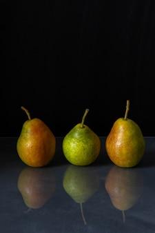 Drie rijpe peren worden weerspiegeld in de tabel
