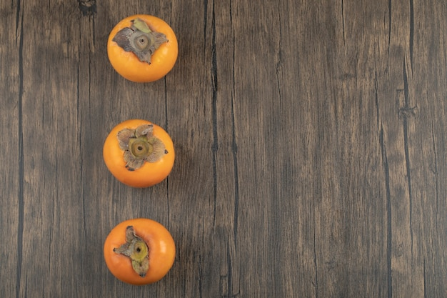 Drie rijpe persimmonvruchten geplaatst op houten oppervlak