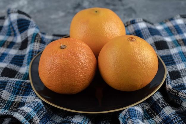 Drie rijpe sinaasappelen op zwarte plaat.