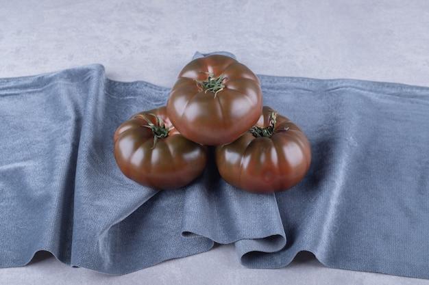 Drie rijpe tomaten op blauwe doek.