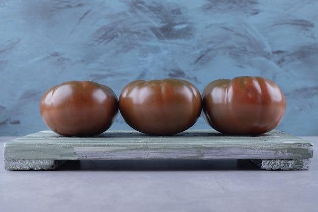 Drie rijpe tomaten op een houten bord.
