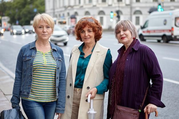 Drie rijpe vrouwen staan op straat in de stad.