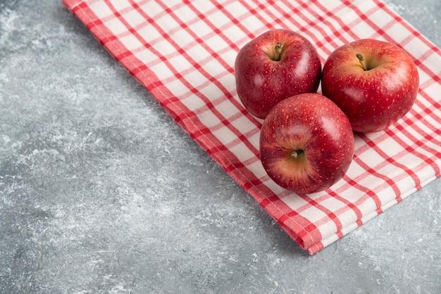 Drie rode appels met gestreept tafelkleed op marmeren oppervlak.
