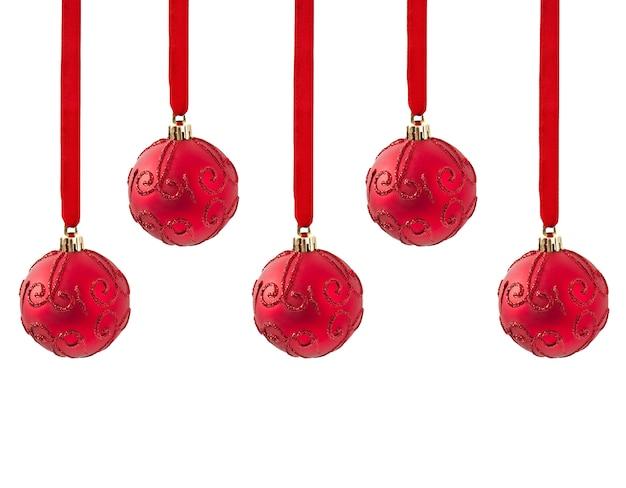 Drie rode ballen die van kerstmis op lint hangen dat op wit wordt geïsoleerd