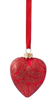 Drie rode ballen die van kerstmis van lint op wit hangen