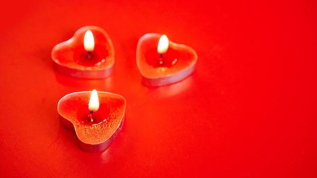 Drie rode brandende kaarsen met hartvormige versieringen op rood. valentijnsdag.