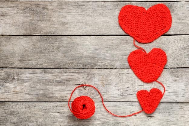 Drie rode gebreide harten, die liefde en familie symboliseren. familierelatie, obligaties.