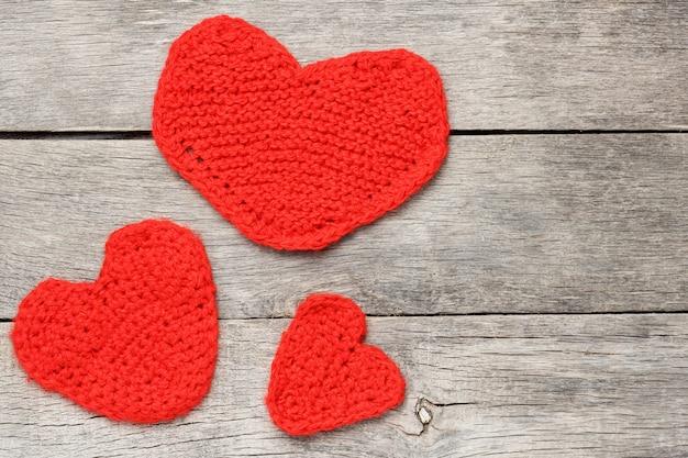 Drie rode gebreide harten, die liefde en familie symboliseren