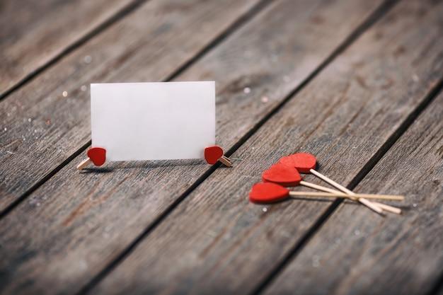 Drie rode harten vormen op stok met papieren kaart op houten achtergrond. valentine-concept copyspace voor tekst.