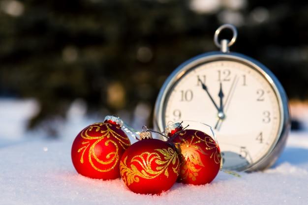 Drie rode kerstballen en wath op een sneeuw.
