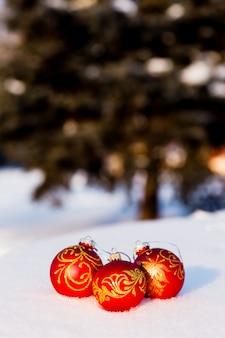 Drie rode kerstballen op sneeuw