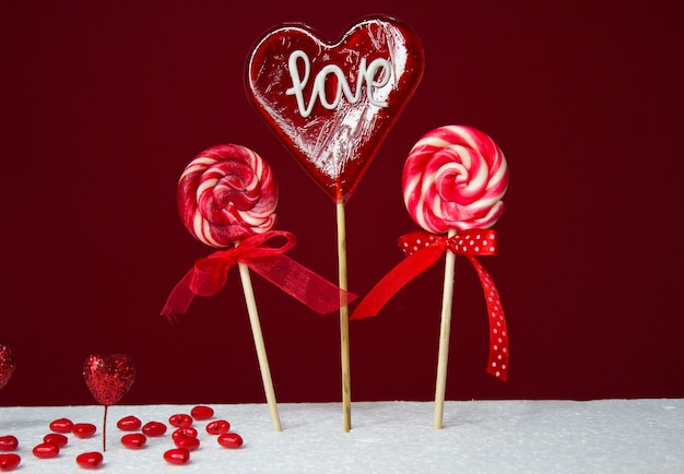 Drie rode lollyjes op rode achtergrond voor valentines, plaats voor tekst