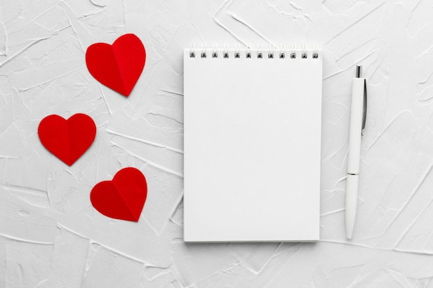 Drie rode papperharten, lege blocnote en pen op witte stopverftextuur. valentijnsdag