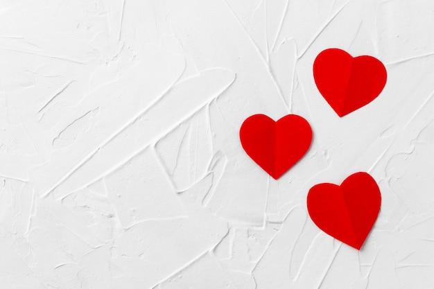 Drie rode papperharten op witte stopverftextuur. valentijnsdag