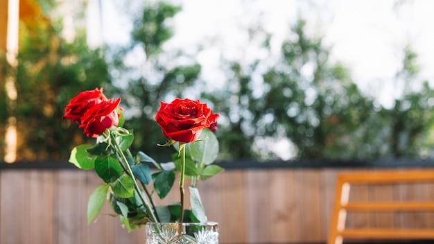 Drie rode rozen in de glazen vaas