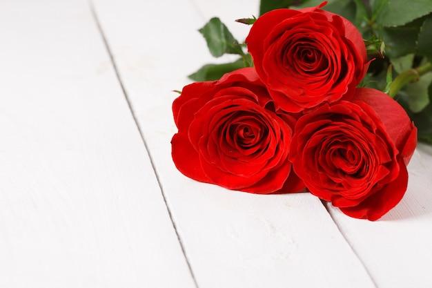 Drie rode rozen liggen op witte houten tafel.