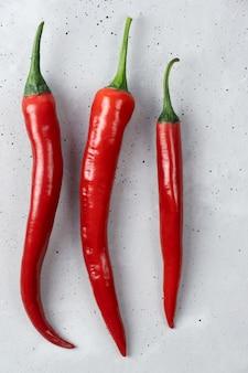 Drie rode verse hete biologische chili pepers liggen op een betonnen tafel.