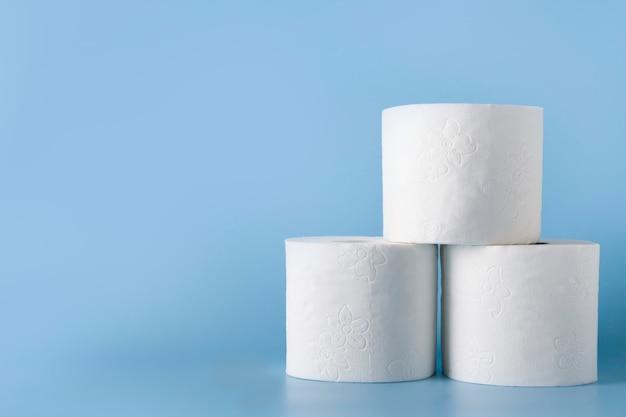 Drie rollen zacht toiletpapier op blauw. covid-19 pandemie. verhoogd potentieel. hoge onverwachte vraag. tekort.