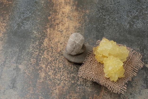 Drie rotsen met plakjes zoete gele suiker op marmeren oppervlak.