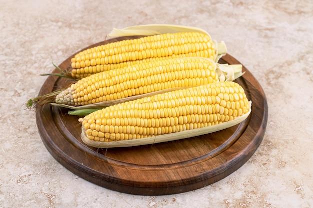 Drie ruwe maïs op houten plaat op marmeren oppervlak