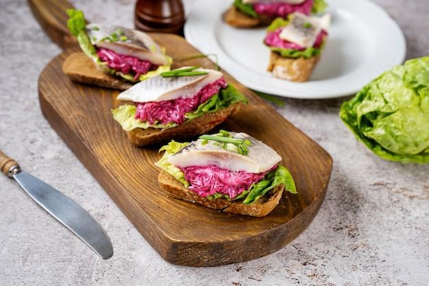 Drie sandwiches met gezouten haring, biet en groene salade