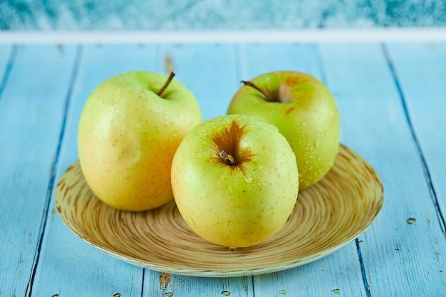Drie sappige appels op keramische plaat en blauwe tafel.