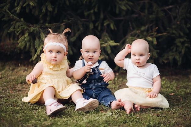 Drie schattige aardige baby's die in lentekleding dragen terwijl ze naar de camera in de tuin kijken. gelukkig concept kindertijd