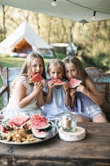 Drie schattige gelukkig lachende meisjes, zussen, duivels, zitten aan de tafel op vintage houten bankje en watermeloen buitenshuis eten