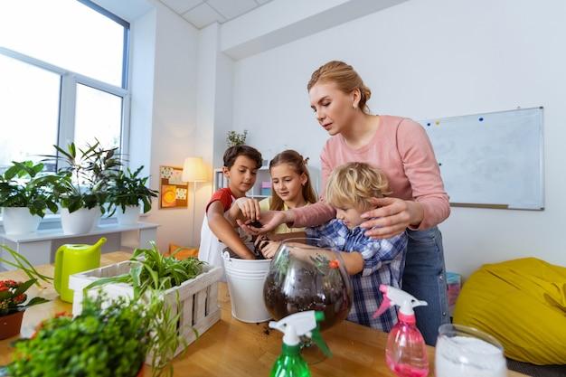 Drie schattige kinderen. drie schattige kinderen die oprecht geïnteresseerd zijn in de les botanie met hun slimme jonge leraar