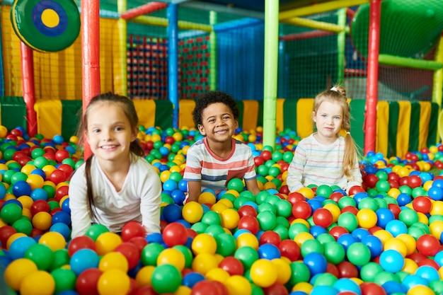 Drie schattige kinderen spelen in de ballpit