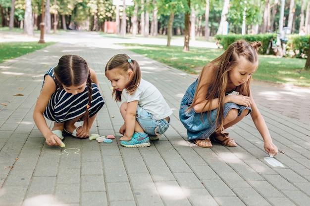 Drie schattige kleine meisjes zitten en tekenen met krijt op asfalt in park
