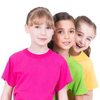 Drie schattige kleine schattige lachende meisjes in kleurrijke t-shirts staan achter elkaar op een witte muur.